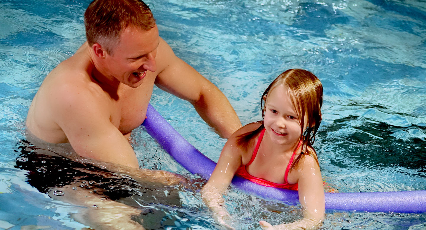 Father with daughter and float in indoor swimming pool