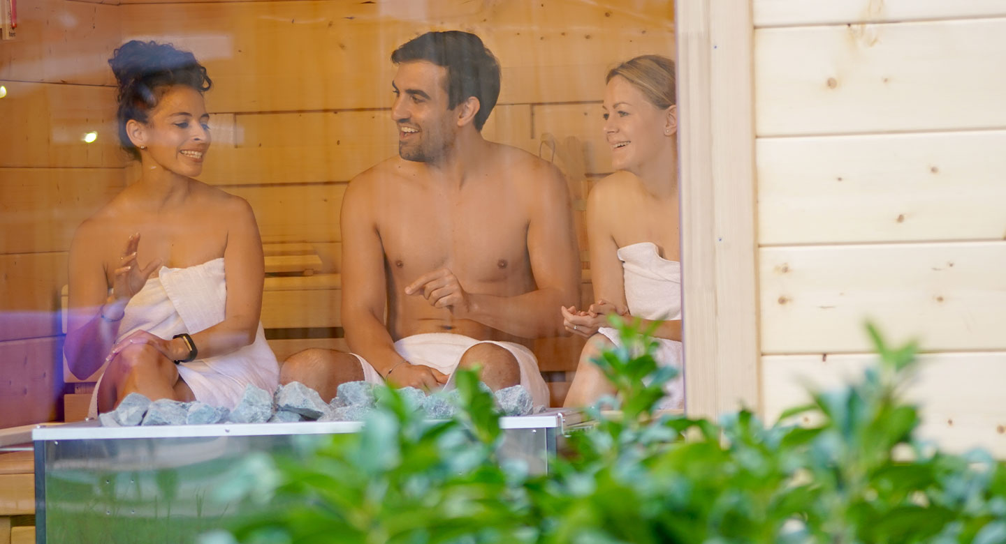 Two women and a man talking in SPA garden sauna