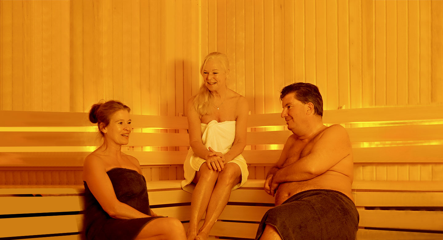 Two women and a man talking in the sauna
