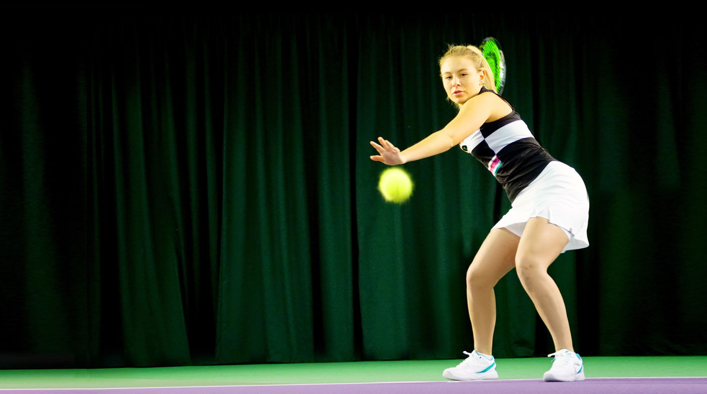 Image of woman hitting forehand on tennis court
