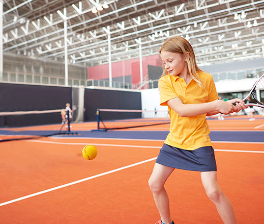 Girl playing tennis at David Lloyd Clubs.